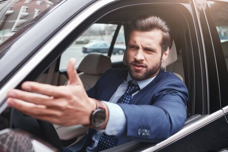 No me gusta Hombre de negocios enojado y emocional en ropa formal está gesticulando y haciendo una mueca mientras conduce su automóvil.
