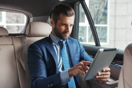 Using modern technologies. Young confident and stylish businessman in formal wear is working on digital tablet while sitting on the back seat of his car.