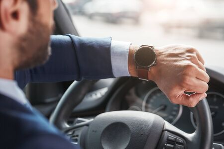 What time is it? Cropped image of bearded businessman is looking at watch on his hand while sitting in the car.