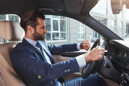 Debería llegar a tiempo. Vista lateral del empresario barbudo confiado y exitoso está mirando el reloj en su mano mientras conduce su automóvil. Foto de archivo