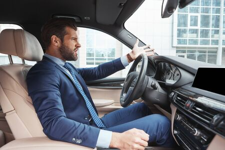 I hate being late! Side view of angry bearded businessman in formal wear is gesturing while driving his car.