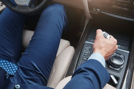 I love my car. Cropped image of businessman in full suit shifting the gear stick while driving his new comfortable car