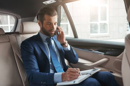 Important talk with client. Busy young businessman in formal wear writing something in his notebook and talking with client by smartphone while sitting on the back seat of his car