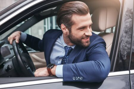 Happy driver. Happy and stylish young businessman in full suit is looking through the window and smiling while sitting in his comfortable car.
