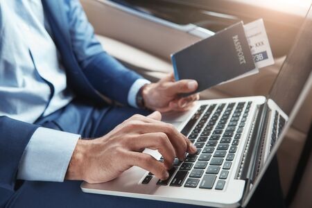 Check in. Cropped image of young businessman in formal wear working on laptop and holding passport with flight tickets while sitting in car.