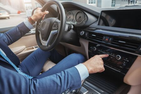 Driving with music. Cropped image of businessman in formal wear pushing buttons of music player while driving to a business meeting Stock Photo