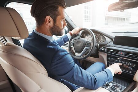 Driving with pleasure. Side view of handsome young bearded businessman in formal wear pushing buttons of music player while driving his car