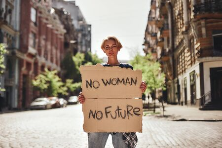 Women power. Young female holding a signboard with word no woman, no future while standing on the road. Protesting outdoors