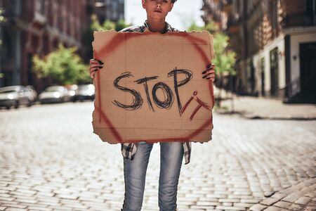 Stop violence. Cropped image of young female holding a signboard with word stop it while standing on the road. Protesting outdoors Stok Fotoğraf