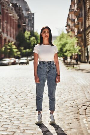 Feeling strong. Vertical photo of young woman in casual clothes standing on the road and looking at camera.
