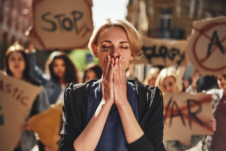 Stop war Young woman with word love written on her face keeping eyes closed and covering her mouth with palms while protesting with group of female activists outdoors on road. Stock Photo