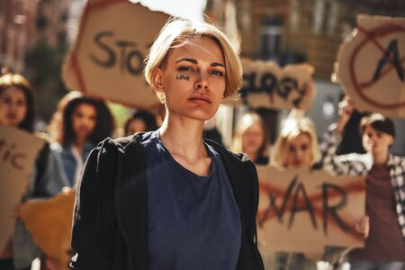 Make love. Young blonde woman with word love written on her face protesting with group of female activists outdoors on road.