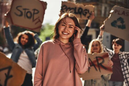 Save your planet. Young woman smiling and feeling happy while protesting for ecology with group of female activists on the road.
