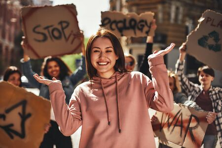 We love our planet. Happy young woman gesturing and smiling while protesting for ecology with group of female activists on the road.