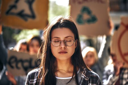 Dreaming about clean earth. Young woman in eyewear keeping eyes closed while standing outdoors in front of female demonstrators on road.