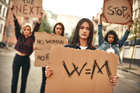 Womens march. Confident and young female protesting for equality and holding a signboard with word w m while standing with other activists on the road