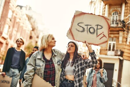 Make peace Young woman in eyewear and casual clothing is holding a banner with word stop it while standing on the road during a womens march aroud female activists