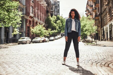 Empty streets. Young Afro American female in casual clothes standing on the road and looking at camera