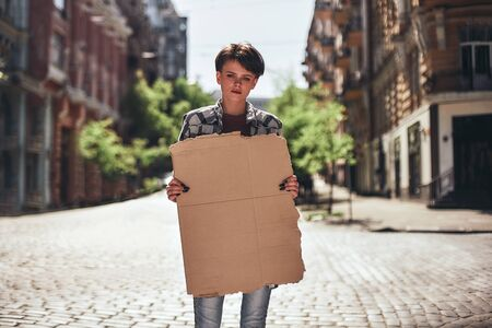 Young woman holding a blank banner and looking at camera while standing on the road. Stock Photo