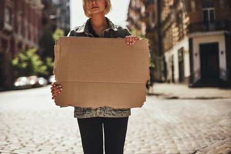 Cropped photo of young woman holding a blank banner while standing on the empty road. Stock Photo