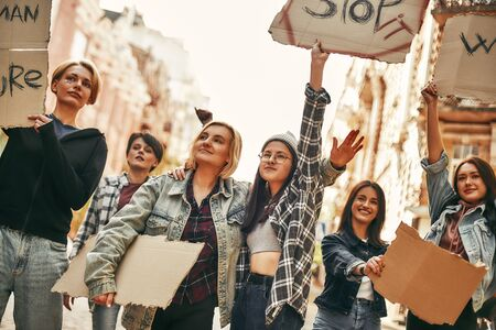 Stop violence against women. Group of young female activists are holding signboards with different slogans while standing on the road during a womens march Stock Photo