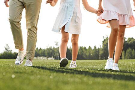 家族の日。手をつないで屋外を歩く3人の幸せな若い家族のトリミングされた写真。幸せな家族の概念。ピクニック。週末