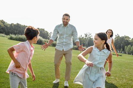 Zeit zum Spielen Glücklicher Vater, der mit seinen Kindern spielt und lächelt, während er seine Freizeit mit der Familie im Freien verbringt