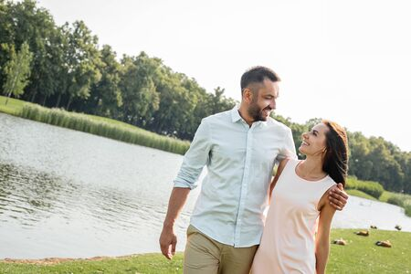 I love my wife Happy young couple smiling and looking at each other while walking outdoors near the river Imagens
