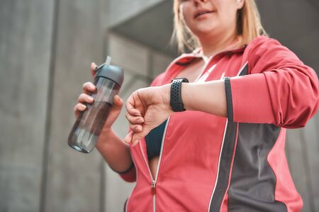 It was great workout. Young plus size woman in sports clothing checking the pedometer and holding bottle of water while standing outdoors