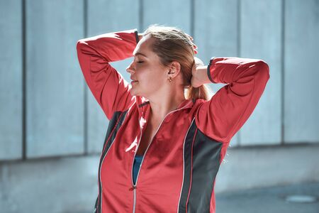 Happy to be myself. Gorgeous plus size woman in sport clothes adjusting hair and looking away while standing outdoors Stock Photo