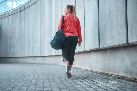 Going home. Back view of plus size woman in sport clothes carrying her bag and going home after exercises outdoors. Sport concept. Fatty women