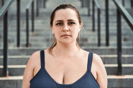 Belleza de talla grande. Retrato de mujer de talla grande en top deportivo de pie en las escaleras y mirando a la cámara Foto de archivo