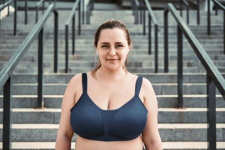 Portrait of cheerful plus size woman in sporty top standing on stairs and looking with smile at camera. Stock Photo
