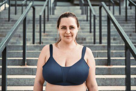 Retrato de mujer alegre de talla grande en top deportivo de pie en las escaleras y mirando con una sonrisa a la cámara.