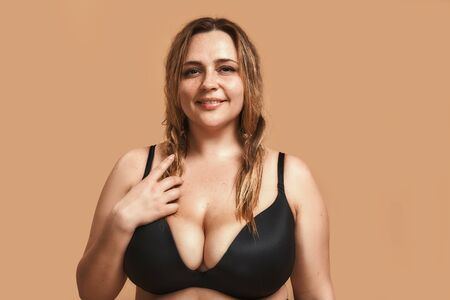 Jolie femme potelée en lingerie noire regardant la caméra et souriant en se tenant debout sur fond marron en studio Banque d'images