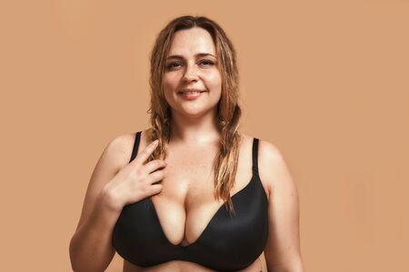 Mujer bonita gordita en lencería negra mirando a cámara y sonriendo mientras está de pie contra el fondo marrón en estudio Foto de archivo