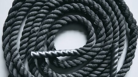 Close up of black battle rope on a gray backgound. Sport and fitness equipment. Functional training Foto de archivo