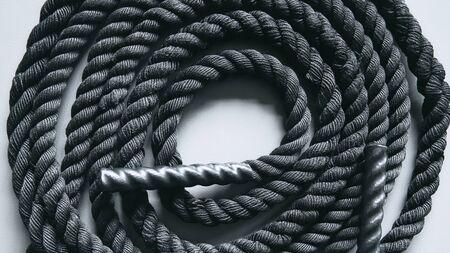 Primo piano di una corda da battaglia nera su uno sfondo grigio. Attrezzature per lo sport e il fitness. Allenamento funzionale Archivio Fotografico