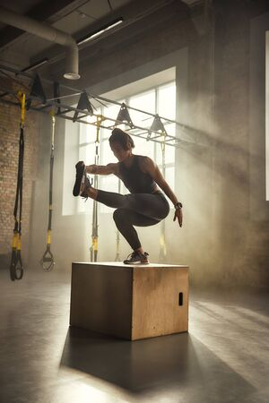 Becoming the best. Side view of athletic woman in sportswear doing squat and training legs while standing on wooden box at gym. Stock Photo