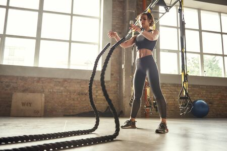 Functional training. Young athletic woman with perfect body doing crossfit exercises with a rope in the gym.