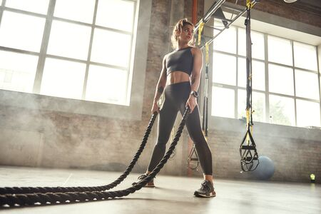 CrossFit training. Young athletic woman with perfect body doing crossfit exercises with a rope in the gym. Stok Fotoğraf