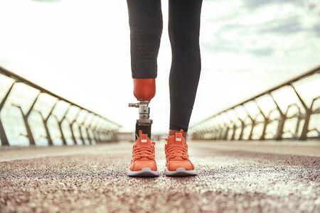 Foto recortada de mujer discapacitada con pierna protésica en ropa deportiva de pie en el puente