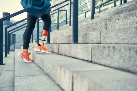 Sport is my way of life. Cropped photo of woman with leg prosthesis in sports clothing carrying her sport bag while standing on stairs outdoors.