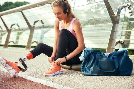 Close up of young woman in sports clothing and headphones with leg prosthesis tying her shoelaces while sitting on the bridge