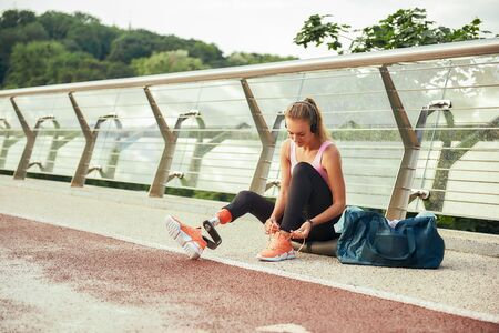 Getting ready to run. Young woman in sports clothing and headphones with leg prosthesis tying her shoelaces while sitting on the bridge