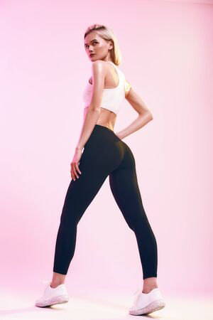 Perfect buttocks. Back view of sporty and cute slim woman with ideal body in sportswear looking at camera while standing against pink background in studio