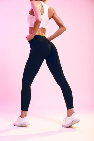 Beautiful buttocks. Back view of sporty slim woman with ideal body in sportswear standing against pink background in studio