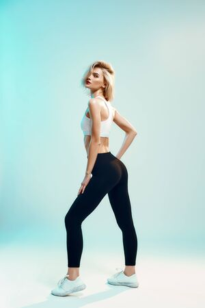 Sporty look. Young woman in white top and black leggings with perfect body is looking at camera while standing against blue background in studio