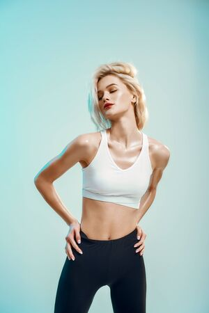 Sporty and beautiful. Young woman in white top and black leggings keeping eyes closed while standing against blue background in studio. Fashion concept. Sensuality. Studio shot