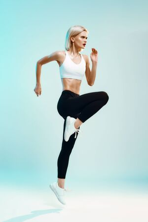 Always in shape. Side view of sporty young woman in white top and black leggings jumping against blue background in studio Stock Photo